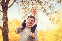 Father and son piggyback in autumn park. Father giving his son piggyback ride in autumn park, Adelaide Hills, South Australia royalty free stock photo
