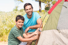 Father and son pitching their tent Royalty Free Stock Photo