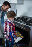 Father and son placing cupcakes tray in oven Royalty Free Stock Image