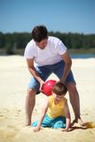 Father with son play with ball on sand. Summer day royalty free stock image