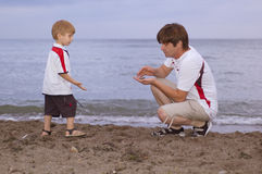 Father and son play on the beach Stock Photography