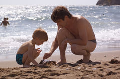 Father with son play on the beach Royalty Free Stock Photos