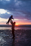 Father and son play on the Beach in sunset, silhouette shot Stock Image