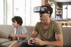 Father And Son Play Computer Game Using Virtual Reality Headset royalty free stock images