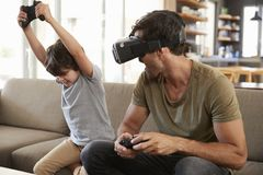 Father And Son Play Computer Game Using Virtual Reality Headset Royalty Free Stock Photos