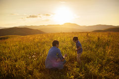 Father and son play on a field at sunset Royalty Free Stock Image