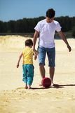 Father with son play football on sand. Summer day stock photography