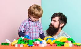 Father and son play game. happy family. leisure time. building home with colorful constructor. child development. father. And son relax. little boy with bearded royalty free stock photo