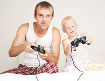 Father and son play. Happy father, and son  relaxing,  and playing with playstation in bed at home Stock Image