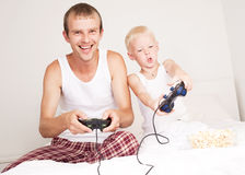 Father and son play. Happy father, and son  relaxing,  and playing with playstation in bed at home Royalty Free Stock Photo