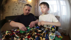 Father and son play LEGO. To work with children. stock footage