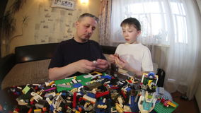 Father and son play LEGO. To work with children. stock video