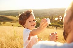 Father and son play with soap bubbles in nature.  Royalty Free Stock Photos