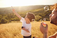 Father and son play with soap bubbles in nature.  Royalty Free Stock Photography