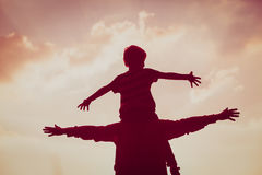 Father and son play on sunset sky Royalty Free Stock Photos