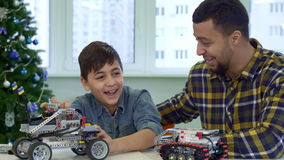 Father and son play with toy SUV stock footage