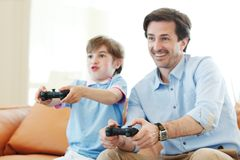 Father and son play video game Stock Photo