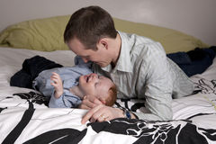 Father and son playing. On bed stock photos