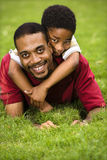 Father and son playing. Father lying in grass smiling as son climbs on his back and hugs his neck Royalty Free Stock Photography