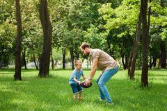 Father and son playing american football. At park stock images