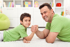 Father and son playing arm wrestling. Happy father and son playing arm wrestling, lying on the floor Stock Photo