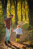 Father and son playing in the autumn forest. Father playing with little son on a picnic in the park in early autumn day. Father playing with little son on a stock photos