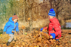Father and son playing in autumn leaves Royalty Free Stock Photos