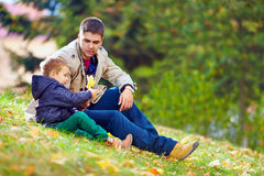 Father and son playing in autumn park Stock Photos