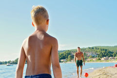 Father and son playing with a ball on the bach near the sea. Man and boy against ocean, active summer holiday vacation Royalty Free Stock Photos