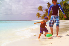 Father and son playing ball at beach Stock Image