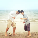 Father and son playing with a ball on the beach Royalty Free Stock Image