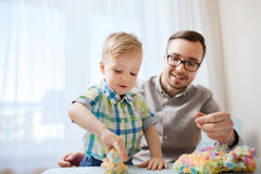 Father and son playing with ball clay at home Stock Image