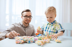 Father and son playing with ball clay at home Stock Photos