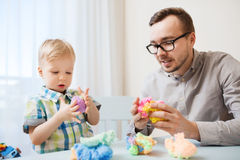 Father and son playing with ball clay at home Royalty Free Stock Images