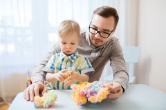 Father and son playing with ball clay at home. Family, childhood, creativity, activity and people concept - happy father and little son playing with ball clay at stock photo