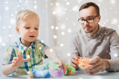 Father and son playing with ball clay at home Stock Photography