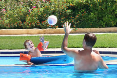 Father and son playing ball in a swimming pool Royalty Free Stock Photography