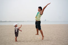 Father and Son Playing On Beach. Asian father and son playing on beach Royalty Free Stock Photo