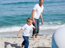 Father and son playing on the beach with balloon Royalty Free Stock Images