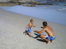 Father and son (4-6) playing on beach, boy running into man's arms, smiling, elevated view Stock Photo