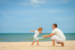 Father and son playing at the beach. At the day time Stock Photography