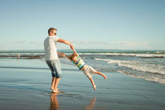 Father and son playing on the beach. At the day time Royalty Free Stock Image