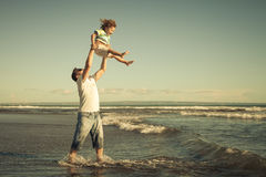 Father and son playing on the beach. At the day time Royalty Free Stock Photos