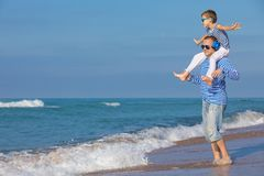 Father and son playing on the beach at the day time. Concept of. Father and son playing on the beach at the day time. They are dressed in sailor`s vests. Concept Stock Image