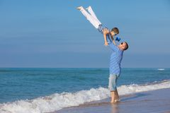 Father and son playing on the beach at the day time. Concept of. Father and son playing on the beach at the day time. They are dressed in sailor`s vests. Concept Stock Photo