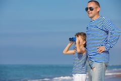 Father and son playing on the beach at the day time. Concept of. Father and son playing on the beach at the day time. They are dressed in sailor`s vests. Concept Stock Photography