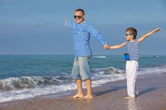 Father and son playing on the beach at the day time. Concept of. Father and son playing on the beach at the day time. They are dressed in sailor`s vests. Concept royalty free stock photos