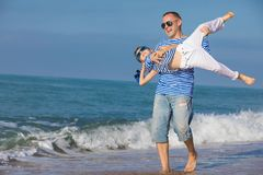 Father and son playing on the beach at the day time. Concept of. Father and son playing on the beach at the day time. They are dressed in sailor`s vests. Concept Royalty Free Stock Photography