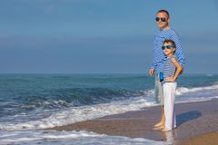 Father and son playing on the beach at the day time. Concept of. Father and son playing on the beach at the day time. They are dressed in sailor`s vests. Concept stock images
