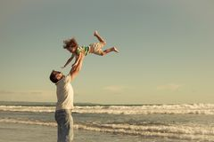 Father and son playing on the beach at the day time. Concept of. Father and son playing on the beach at the day time. People having fun outdoors. Concept of Stock Photography